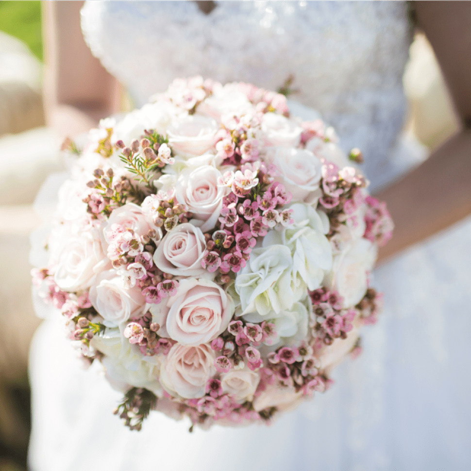 pink and white floral bouquet held by bride
